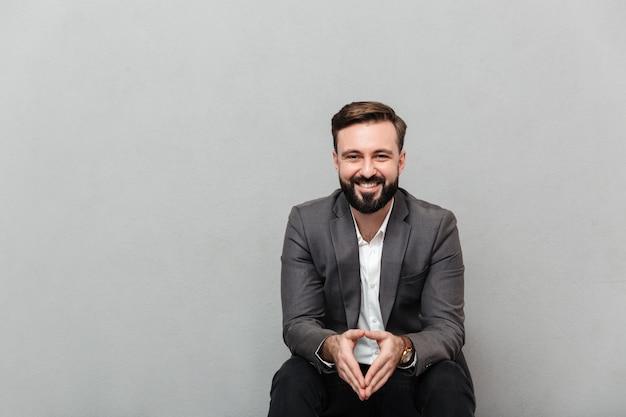 Ritratto potato dell'uomo rilassato che riposa mentre sedendosi sulla sedia in ufficio e sorridendo sulla macchina fotografica che un le mani, isolato sopra grey Foto Gratuite