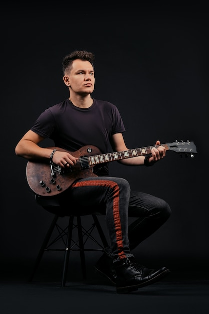 Ritratto scuro dell'uomo che canta e che gioca elettro chitarra Foto Premium