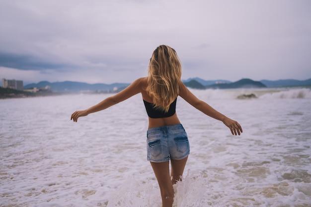 Ritratto sensuale della donna bionda che sta e che posa con a braccia aperte indietro sulla spiaggia all'oceano tempestoso del mare. forti onde e vento nei capelli. in viaggio lungo l'asia, concetto di stile di vita attivo Foto Premium