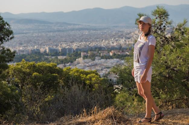 Ritratto sognante e aria attraente ragazza in un cappello di essere giocoso e spensierato con un bel sorriso in giornata di sole della città di atene con il monte licabetto, in grecia, come visto dall'aria. Foto Premium