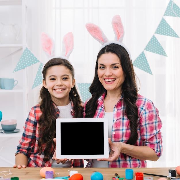 Ritratto sorridente della madre e della figlia che mostrano compressa digitale dietro la tavola di legno con le uova di pasqua Foto Gratuite