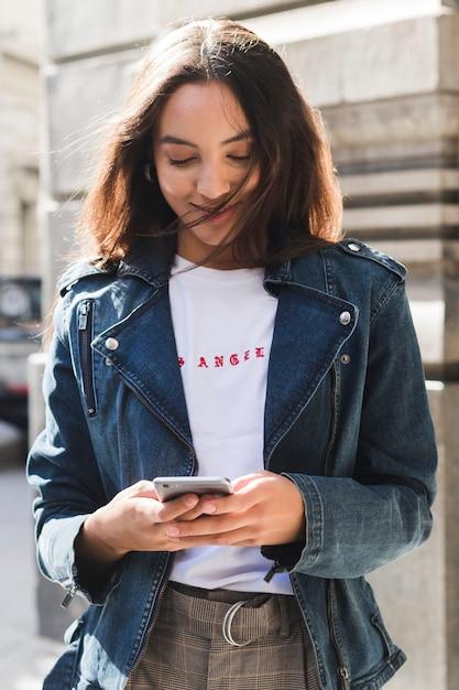 Ritratto sorridente di giovane donna alla moda che per mezzo del telefono cellulare Foto Gratuite