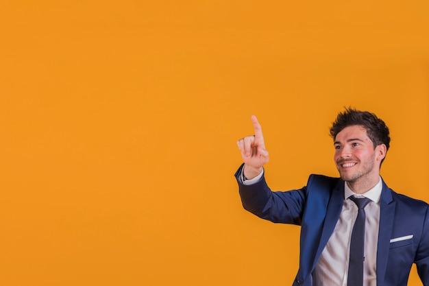 Ritratto sorridente di giovane uomo d'affari che indica la sua barretta a qualcosa su una priorità bassa arancione Foto Gratuite