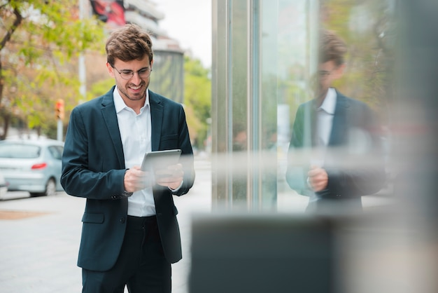 Ritratto sorridente di giovane uomo d'affari facendo uso della compressa digitale all'aperto Foto Gratuite
