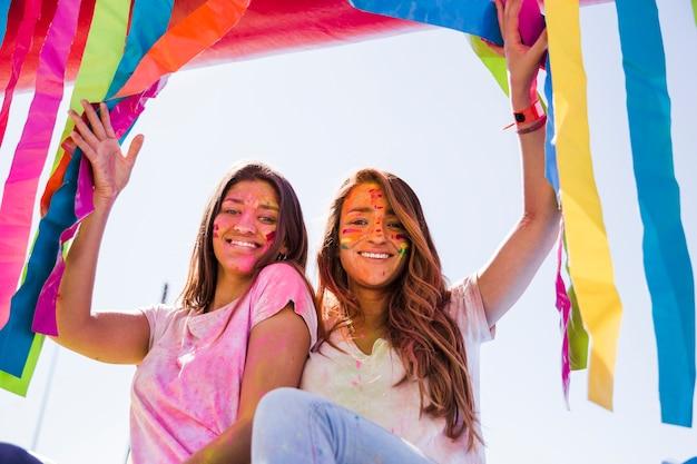 Ritratto sorridente di giovani donne con colore di holi sul loro fronte che guarda l'obbiettivo Foto Gratuite
