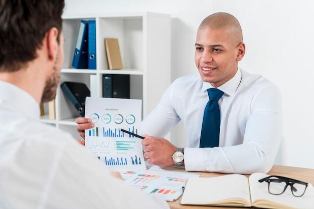 Ritratto sorridente di un giovane uomo d'affari che discute il grafico con il suo collega nel luogo di lavoro Foto Gratuite