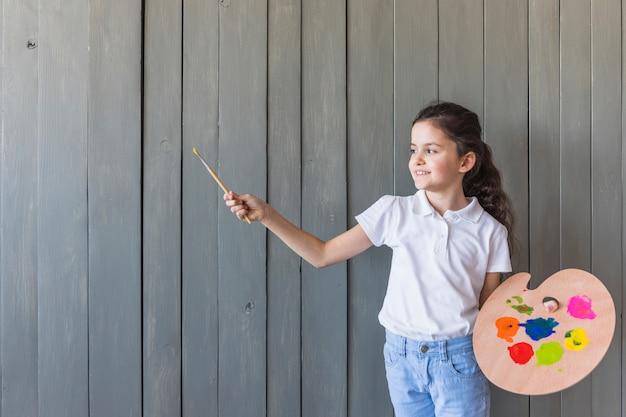 Ritratto sorridente di un pennello e di una gamma di colori della tenuta della ragazza a disposizione che stanno contro la parete di legno grigia Foto Gratuite