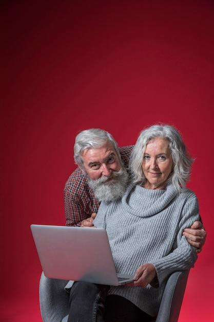 Ritratto sorridente di un uomo anziano che abbraccia la sua moglie da dietro seduto sulla sedia con il portatile Foto Gratuite
