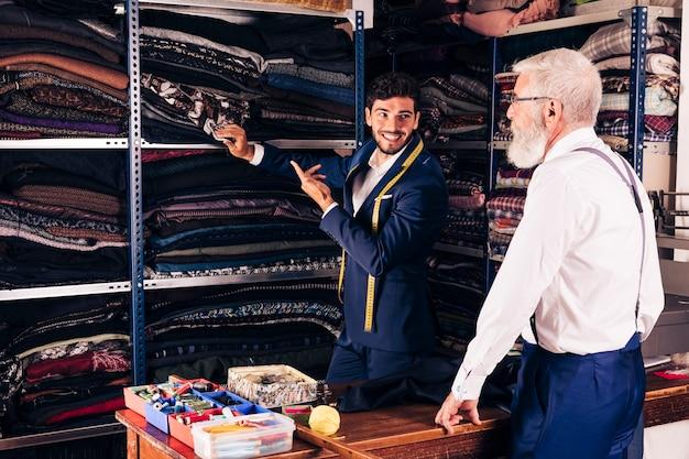 Ritratto sorridente di un uomo che mostra tessuto al suo cliente maschio senior nel negozio Foto Gratuite