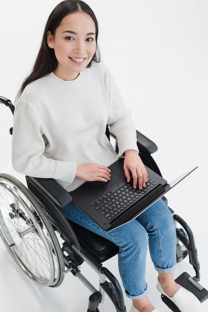 Ritratto sorridente di una giovane donna che si siede sulla sedia a rotelle con il computer portatile sul suo giro che guarda l'obbiettivo Foto Gratuite