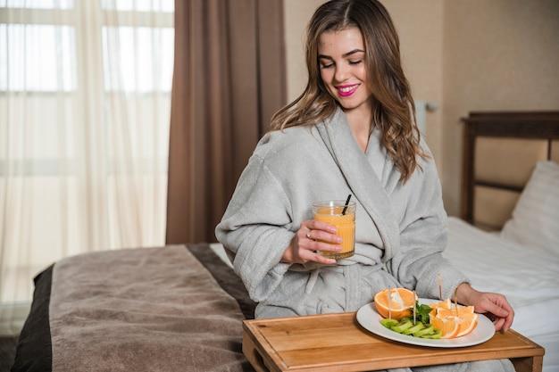 Ritratto sorridente di una giovane donna in accappatoio che si siede sul letto che ha prima colazione sana fresca Foto Gratuite