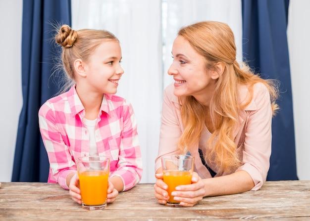 Ritratto sorridente di una madre e sua figlia che tengono vetro di succo che se lo esamina reciprocamente sulla tavola di legno Foto Gratuite