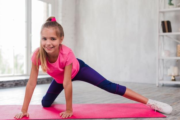 Ritratto sorridente di una ragazza bionda che si esercita sulla stuoia rosa Foto Gratuite