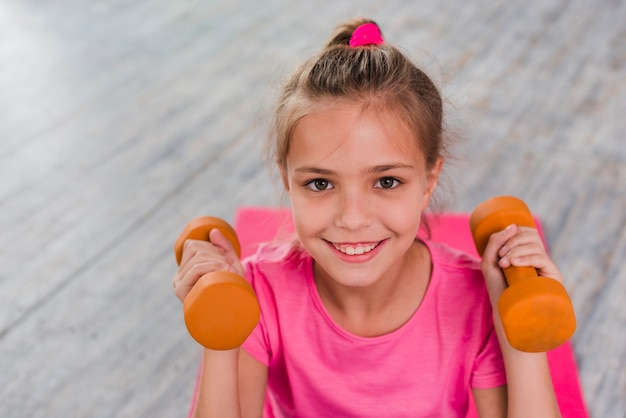 Ritratto sorridente di una ragazza che fa esercitazione con il dumbbell Foto Gratuite