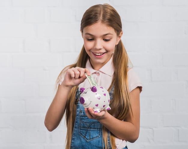 Ritratto sorridente di una ragazza che inserisce la nota di valuta nel porcellino salvadanaio bianco Foto Gratuite