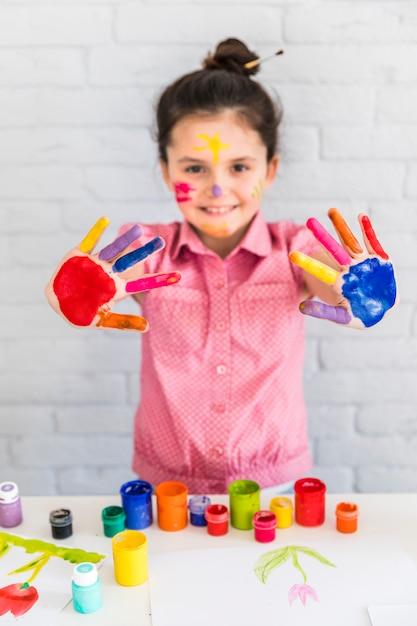 Ritratto sorridente di una ragazza che mostra la sua mano colorata dipinta Foto Gratuite
