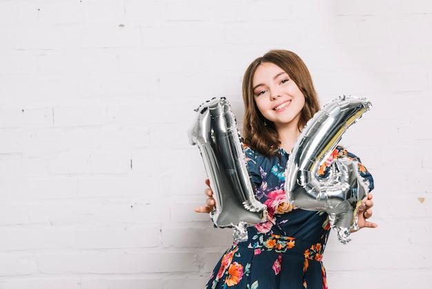Ritratto sorridente di una ragazza che mostra pallone di stagnola di numero 14 Foto Gratuite