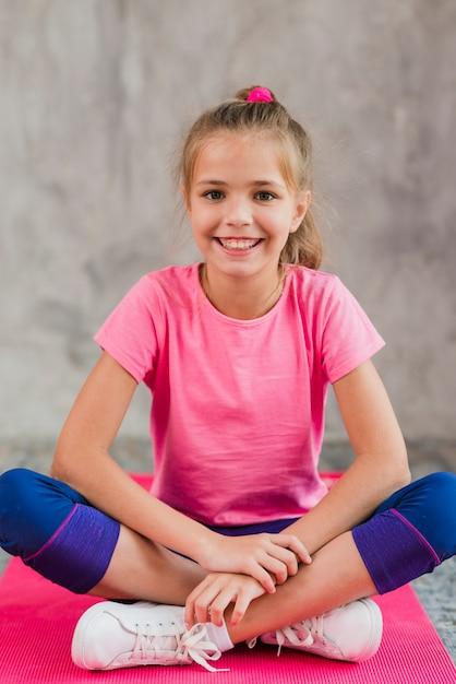 Ritratto sorridente di una ragazza che si siede sul tappeto rosa contro il muro di cemento grigio Foto Gratuite