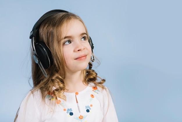 Ritratto sorridente di una ragazza con la cuffia che distoglie lo sguardo contro il contesto blu Foto Gratuite
