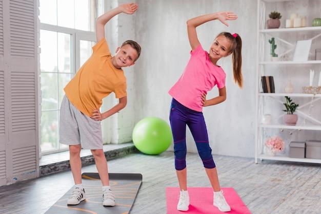 Ritratto sorridente di una ragazza e di un ragazzo che stanno sull'allungamento della stuoia di esercizio Foto Gratuite