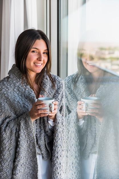 Ritratto sorridente riflettente della tazza di caffè della tenuta della donna a disposizione Foto Gratuite