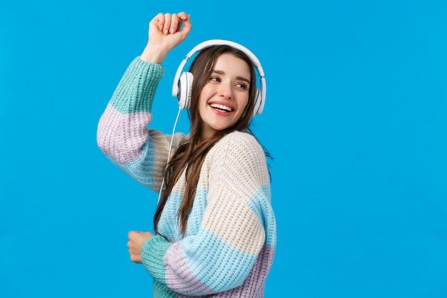 Ritratto spensierato, donna danzante felice in cuffia, sorridente alzando le mani in alto e ottimista, godendo le canzoni preferite, speciali vacanze invernali playlisty, ridendo con gioia, blu Foto Premium