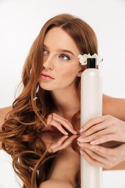 Ritratto verticale di bellezza della donna dello zenzero con il fiore in capelli che si siedono dalla tavola dello specchio con la bottiglia di lozione mentre distogliendo lo sguardo Foto Gratuite