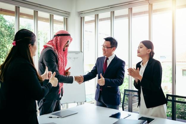 Riunione d'affari squadra asiatica e uomo arabo che presenta le sue idee in ufficio Foto Premium