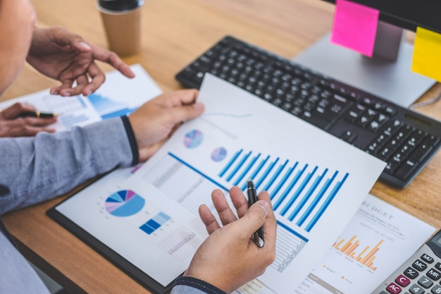 Riunione del gruppo di affari che lavora con il nuovo progetto di avvio, discussione e dati di analisi le tabelle ed i grafici, usando del calcolatore Foto Premium