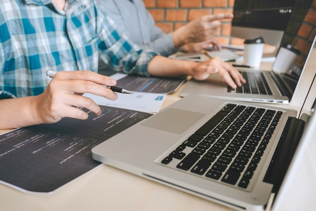 Riunione di cooperazione con programmatori di sviluppatori professionisti, brainstorming e programmazione in un sito web che lavora su una tecnologia di outsourcing e codifica software, scrittura di codici e database Foto Premium
