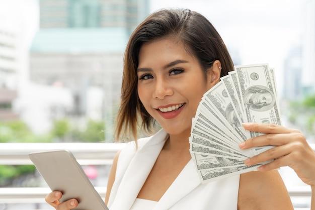 Riuscita bella giovane donna asiatica di affari che usando le fatture del dollaro americano dei soldi e dello smart phone a disposizione Foto Gratuite