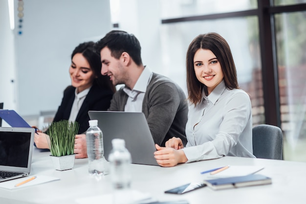Riuscita femmina che utilizza computer portatile sul suo lavoro nell'ufficio. Foto Premium