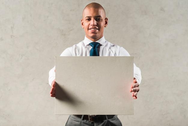 Riuscito giovane uomo d'affari che mostra cartello grigio che sta contro la parete Foto Gratuite