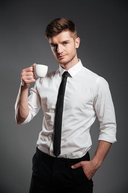 Riuscito uomo d'affari in abbigliamento formale che tiene tazza di caffè mentre stando Foto Gratuite