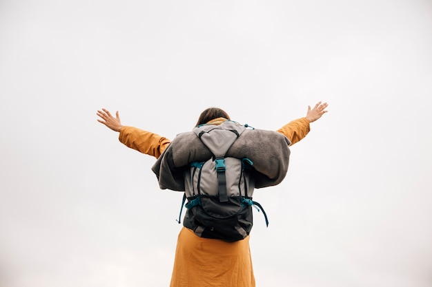 Riuscito viaggiatore con zaino e sacco a pelo della giovane donna a braccia aperte contro il cielo Foto Gratuite