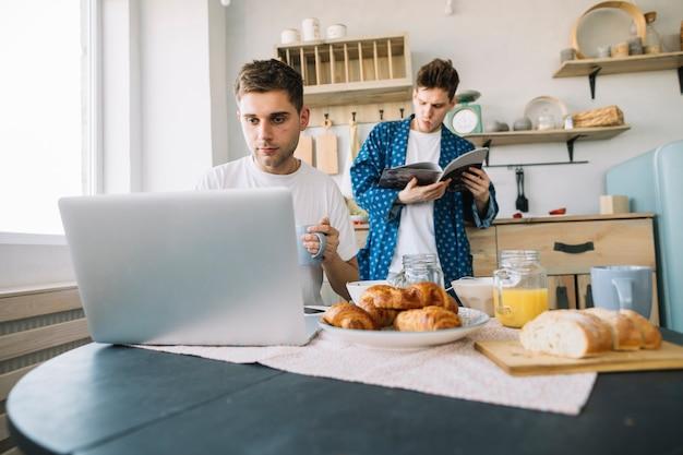 Rivista della lettura del giovane che sta dietro il suo amico che lavora al computer portatile con la prima colazione sul tavolo Foto Gratuite