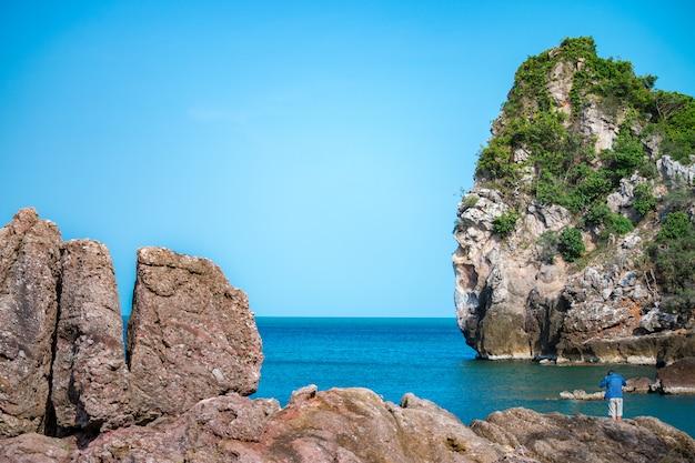 Rocce, pescatore, mare e cielo blu Foto Premium