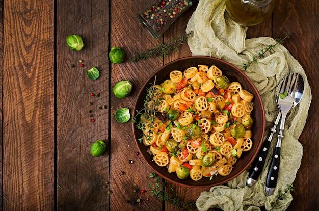 Rocchetti di verdure vegetariano pasta con cavoletti di bruxelles, pomodoro, melanzane e paprika in ciotola marrone sul tavolo di legno. vista dall'alto Foto Premium