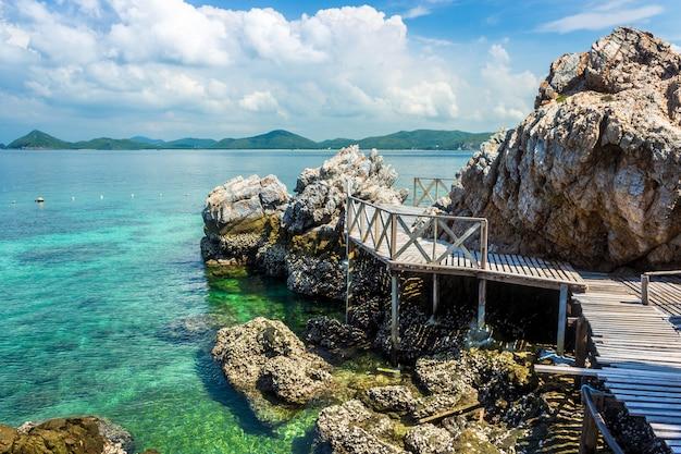 Roccia tropicale dell'isola e ponte di legno sulla spiaggia con cielo blu. Foto Premium