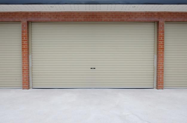 Roll porta in acciaio o porta dell'otturatore e pavimento in cemento al di fuori dell'edificio di parcheggio di casa. Foto Premium