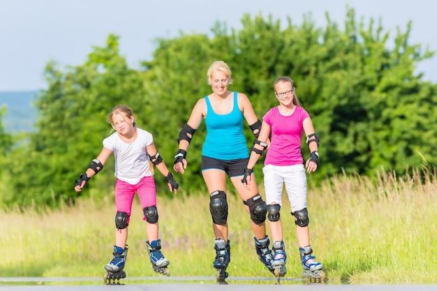 Rollerblade familiare con pattini sulla corsia di campagna Foto Premium