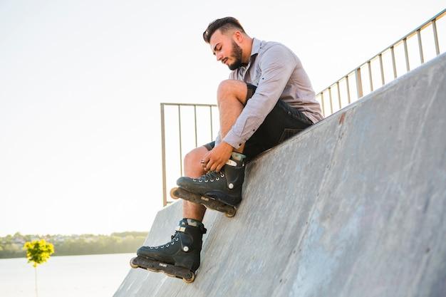 Rollerskater maschio che mette sui rollerskate in skate park Foto Gratuite