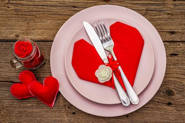 Romantico tavolo da pranzo con piatti e tovagliolo a forma di cuore Foto Premium
