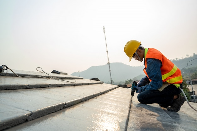 Roofer di ispezione dell'uniforme di sicurezza di usura di ingegnere di costruzione che lavora alla struttura di tetto di costruzione sul cantiere. Foto Premium