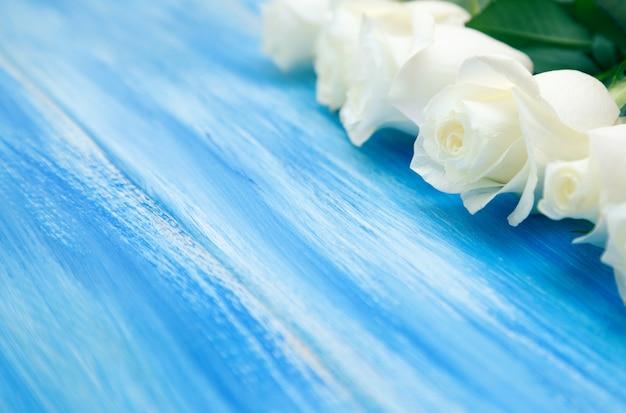 Rosa bianca. un bouquet di rose delicate su uno sfondo blu di legno Foto Premium
