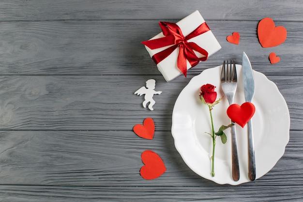 Rosa rossa con posate sul piatto bianco Foto Gratuite