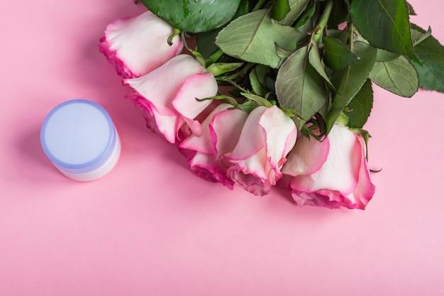 Rose e crema per il viso di fioritura rosa sul rosa pastello. cornice floreale romantica per la cura della pelle. copia spazio Foto Premium