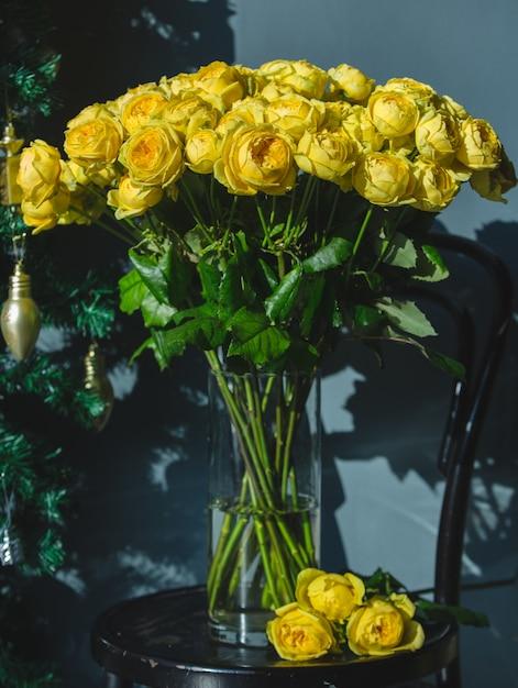 Rose gialle all'interno del vaso di vetro trasparente con acqua sulla sedia. Foto Gratuite