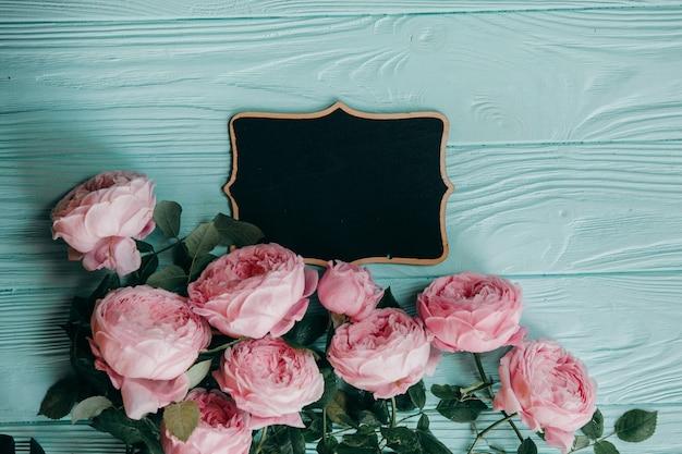 Rose rosa e una cornice su un tavolo blu Foto Premium