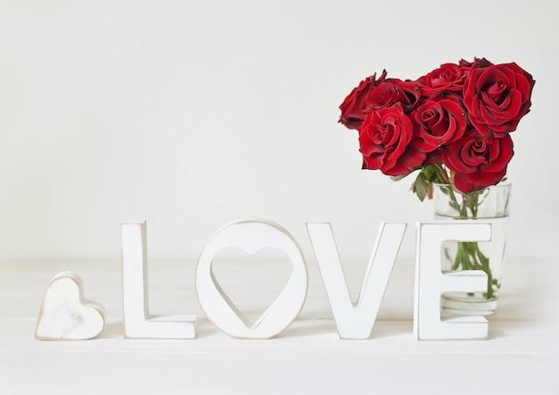 Rose rosse con cuore, lettere in legno amore, modello di cartolina Foto Premium